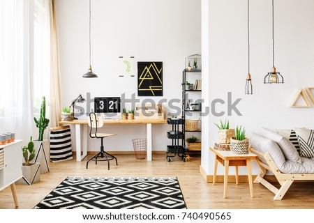 Black and white geometric carpet in multifunctional workspace with artwork on wall above desk #740490565