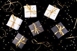 Black and white gift boxes with gold ribbon on shine background. Flat lay