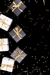 Black and white gift boxes with gold ribbon on shine background. Flat lay. Copy space