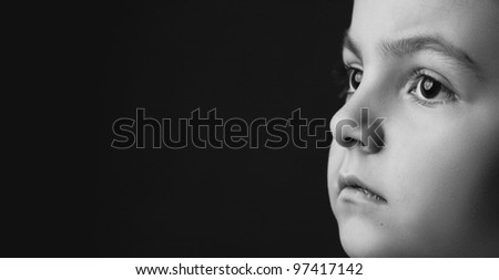 black and white girl's face on black background is thinking and looking away