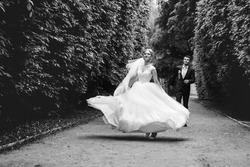 Black and white gorgeous stylish blonde bride in vintage white dress and elegant groom posing in the park