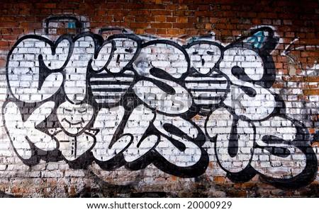 stock photo : Black and white graffiti inscription Crisis Kills Us on brick