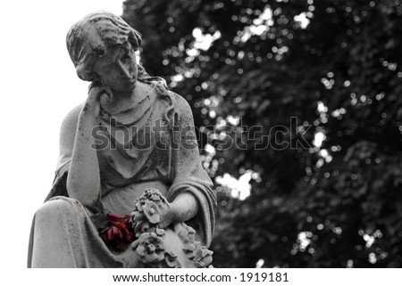 Black and White Granite statue of woman holding a colored red rose at gravesite