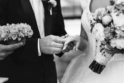 Black and white groom and beautiful bride exchanging wedding rings closeup