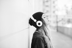 Black and white half length profile portrait of young handsome caucasian blonde hair woman leaning against a wall, listening music with headphones, eyes closed - serene, enjoying, music concept