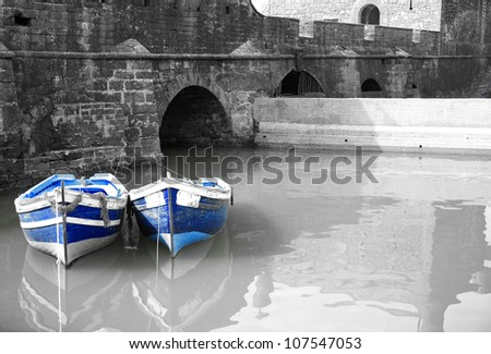 Black and white harbour with two blue boats Essaouria Morocco