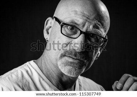 black and white head shot of a middle aged stern looking bald man with facial hair looking into camera wearing glasses with a black background