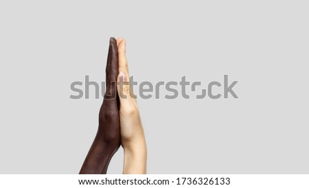 Black-and-white human hands touch palms to show each other friendship and respect. The concept of combating racism. Banner, copy space.