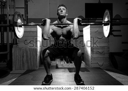 Black and White image. A very dramatic image that conveys motivation, determination, and focus. The dramatic lighting really adds to the image. Strong, attractive, male exercising with weights.