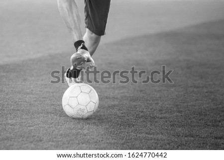 Photo of Black and white image. Blurry ball after  soccer player speed run on green artificial turf to shoot it to goal. Soccer player training. Asian player in football academy.