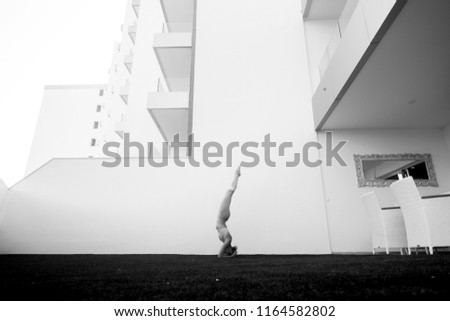 black and white image fine art representing beautiful thin babe female young athlete doing yoga and pilates positions outside home in a garden with all the building in background.  #1164582802