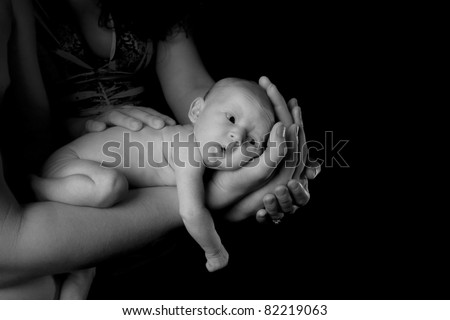 Black and White image of a baby being held by her parents.