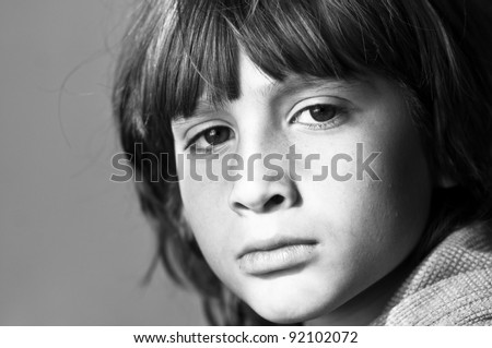 Black and white image of a boy with his sad facial expression. Image signaling to stop violence against children.