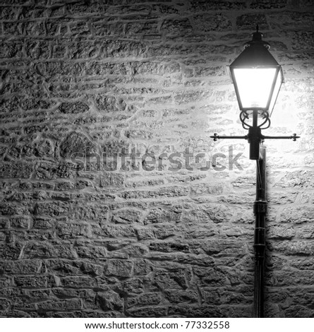 Black and white image of a brightly lit Lamp post against a textured brick wall at night. Lack of color highlights texture in the wall