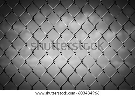 Black and White Image of a Chain Link Fence against a Cloudy Sky with Vignette #603434966