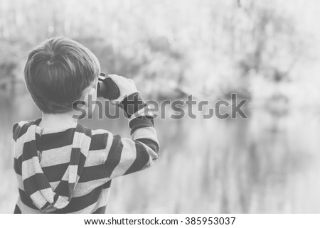 Photo of Black and white image of a child looking through binoculars at a river and forest.