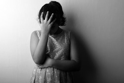Black and white image of a disappointed girl placing her fingers on forehead. One light studio shot with shadow