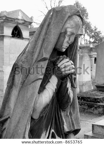 black and white image of a praying woman sculpture in parisian cemetery of Pere Lachaise