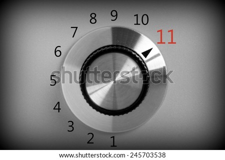 Black and white image of a volume or power control switch on a metal background that goes all the way up to the number eleven. #245703538