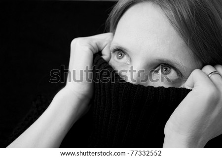 Black and white image of a young, pretty woman partially covering her mouth and nose with her sweater, looking up and out of the frame towards black background with copy space