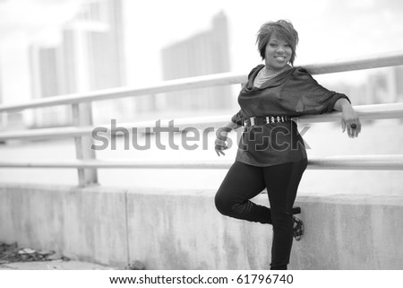 Black and white image of a young woman leaning on a guard rail