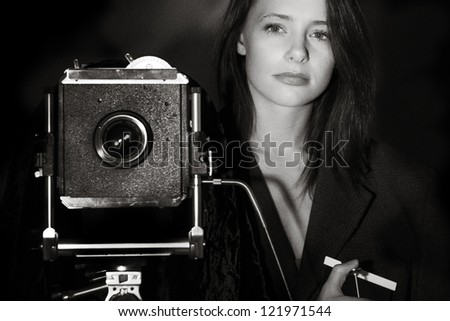 black and white image of a young woman taking a photography with a large 5x4 film camera