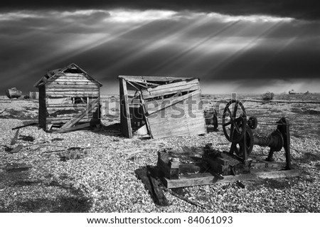 black and white image of abandoned sheds, winding gear, equipment and fishing boats on the shingle beach at Dungeness, England with a stormy, moody sky beyond.