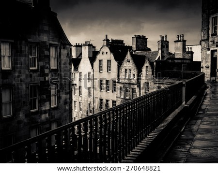 Black And White Image Of An Ancient Edinburgh Street Under A Stormy Sky