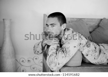 Black and white image of an attractive young man relaxing on a sofa while on holiday.