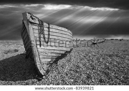 black and white image of an old wooden fishing boat left to rot and decay on the shingle beach at Dungeness, England, UK.
