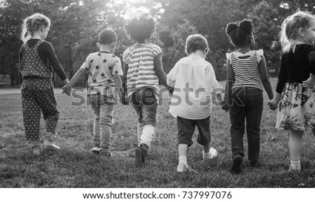 Black and white image of children walking at the park #737997076