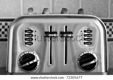 Black and white image of classic retro styled toaster with sliced bread.  Decorative tiled backsplash in background. - stock photo
