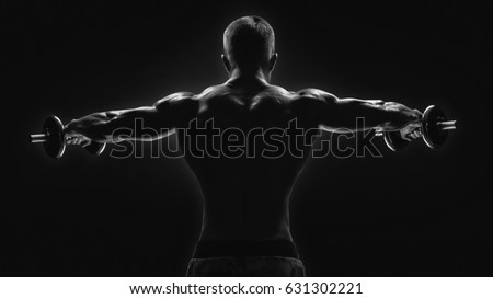 Black and white image of dumbbell lateral raise routine Bodybuilder turning back raising hands pumping up shoulders muscle exercise Power Partials routine with dumbbells on gym Dramatic studio shot