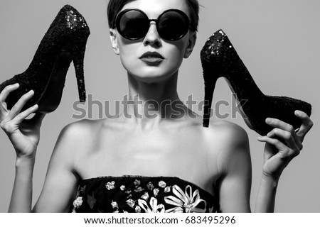 Black and white image of fashion woman wearing sunglasses hold high heels  #683495296