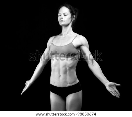 Black and white image of female athlete posing against black background. Some grain added.