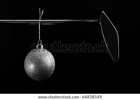 Black and white image of golf putter with Christmas ornament hanging