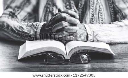 Black and white image of Hands of old woman with  Holy book  and eyeglass on table .Concept of peaceful and Calmness in Meditation.