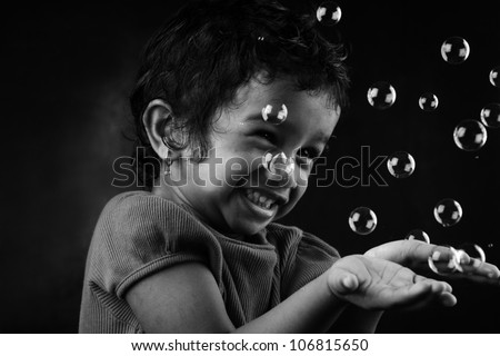 Black and white image of happy little girl playing with bubbles