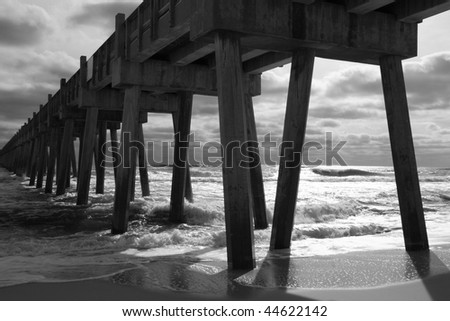 Black and white image of heavy surf crashing against the Pensacola Beach fishing pier on Santa Rosa Island, Florida, the longest pier on the Gulf of Mexico