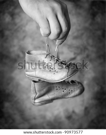 Black and white image of Man holding his old baby shoes in his hand.