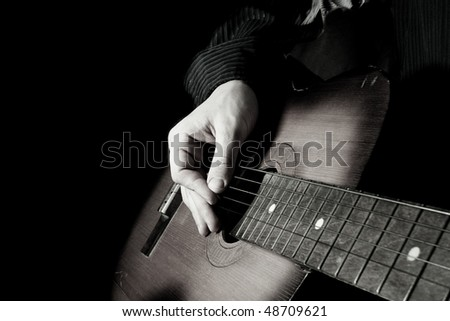 black and white image of man playing guitar