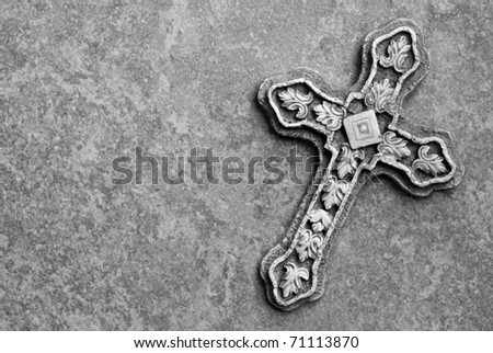 Black and white image of ornate stone cross on marble background with copy space.