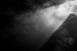 Black and white image of ray of light through clouds