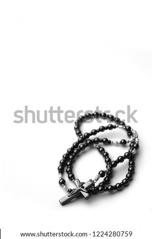 black and white image of rosary beads against a stark white background