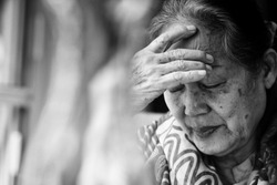 Black and white Image of 60s or 70s  Asian elderly woman facepalm or cover her face by her hands .She may had Headache Symptoms.She looks pain or sick or crying.Sad elderly or self isolated concept.