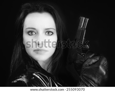 Black and white image of secret agent woman with gun in hand on black background