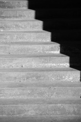 black and white image of shadow cast on staircase rigid angles lines going up or down on grey cement stairs contrast in illusion and perception  vertical format background room and space for type