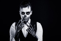 Black and white image of skull make up portrait of young man in studio.