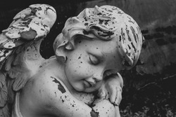 Black and white image of sleeping putto or child angel figurine on a grave, horizontal, copy space for text