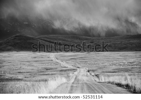 Black-and-white image of storm cloud over barren landscape with mountains in the background. A dirt road recedes across Montana's National Bison Refuge. Horizontal shot.